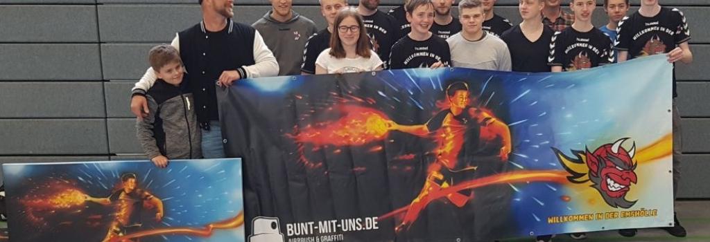 Graffiti- und Airbrushkünstler Maximilian Ziegner (2.v.l.) überreichte dem HF-Fanclub das von ihm entworfene Banner, das die Einheizer jetzt optisch in der Emssporthalle unterstützt. (Foto: Handballfreunde)